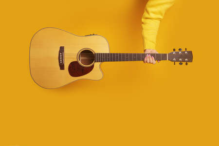 guitar in hand over yellow background, mock-up image