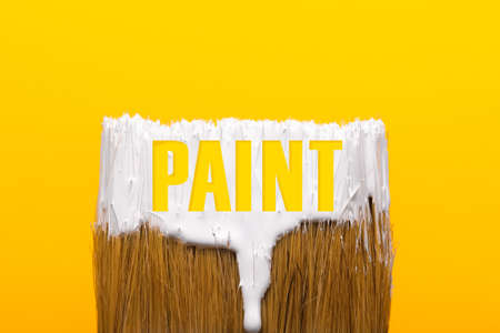 Paintbrush with white paint over yellow background, repair and painting tool concept