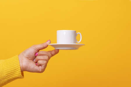 coffee cup in hand over yellow background