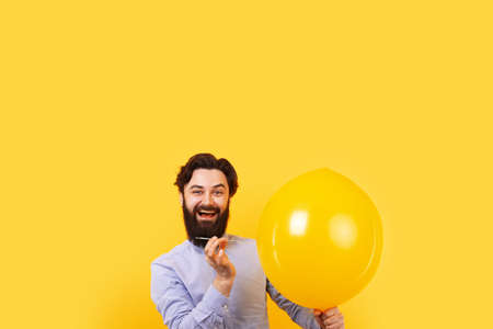 Man holding needle over yellow air balloon, a moment before bubble burst. 免版税图像