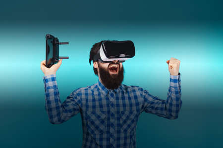 bearded man rejoices victory in glasses of virtual reality over blue background