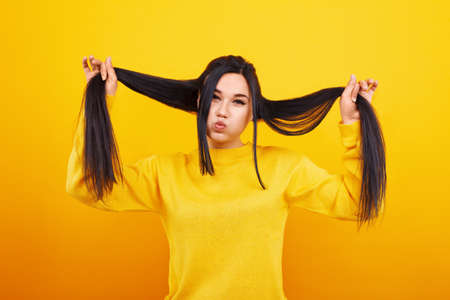 A girl with long hair fooling over yellow 免版税图像 - 152977320