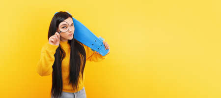 Girl with a skateboard and a magnifier over yellow 免版税图像 - 152977319