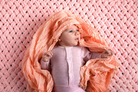 A baby in a pink suit on a knitted plaid