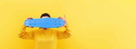Girl with skateboard over yellow 免版税图像 - 152977461