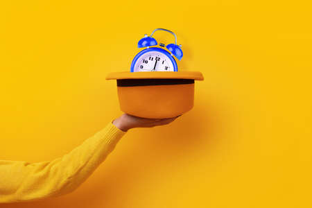 Fashionable yellow felt hat with blue clock on hand over yellow