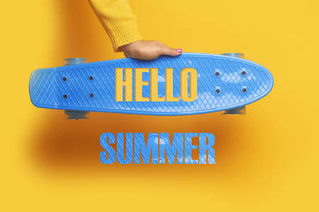 Blue skateboard in hand over yellow