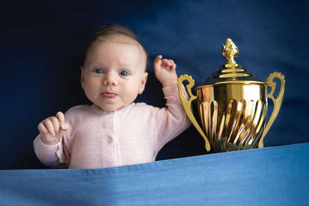 A baby with golden cup, victory concept