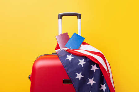 Passports with USA flag on red suitcase.