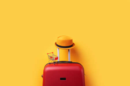 Hat on suitcase with shopping cart over trend yellow 免版税图像 - 152977477