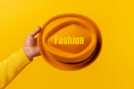 Yellow felt hat in hand with inscription fashion over yellow 免版税图像 - 152977565