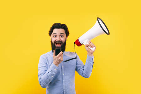 Cheerful man with megaphone over yellow