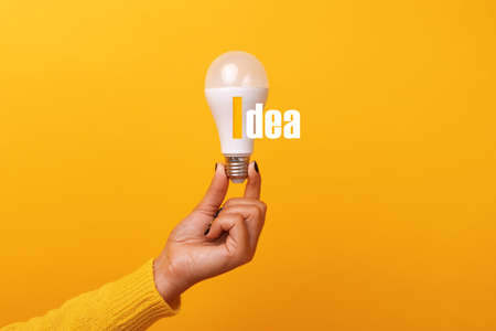 light bulb in hand with inscription idea over yellow background 免版税图像 - 153679704