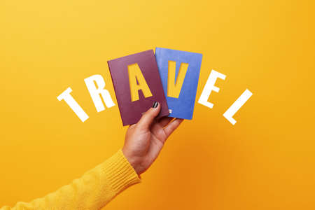 Hand holding two passports over yellow background, travel concept