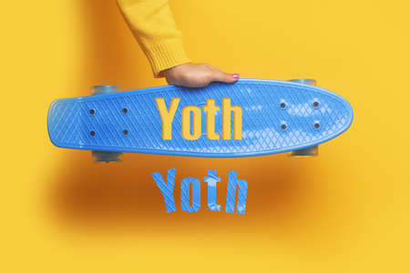yoth inscription on blue skateboard, image over yellow background