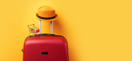 concept of shopping abroad, hat at suitcase with shopping cart over trend yellow background, panoramic mock up image 免版税图像