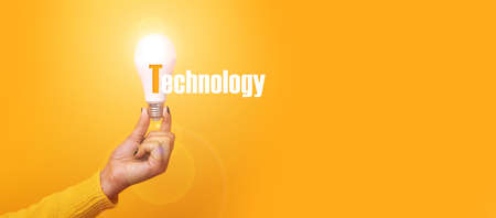 hand holding light bulb with inscription technology, illuminated light bulb, panoramic mock up over yellow background 写真素材