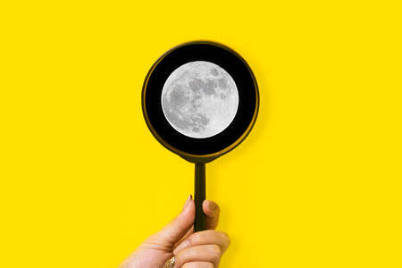 moon under a magnifying glass, space exploration concept