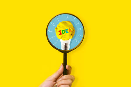 Creative idea and innovation concept with magnifier in hand on yellow background
