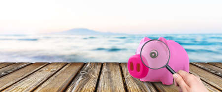 pink piggy bank over background of sea, concept of finding money for a vacation trip