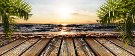 empty wooden table on the background of the seascape at sunset, panoramic image