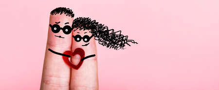 fingers with painted faces in glasses on a pink background, concept of an engaged couple, blank for Valentine's Day