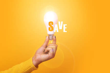 illuminated light bulb with inscripton save over yellow background