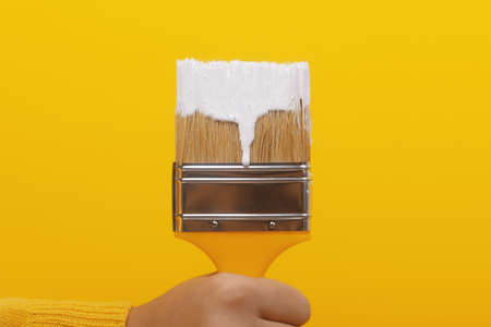 paint brush with white paint in hand on yellow background