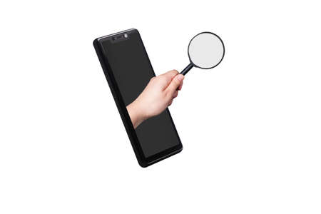 Hand holding magnifying glass, sticking out of the smartphone screen, phone search concept 免版税图像