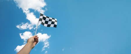 checkered race flag in hand over blue sky 免版税图像
