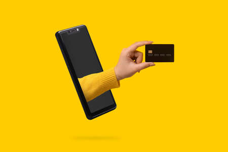 bank card in hand sticking out of the smartphone screen 免版税图像