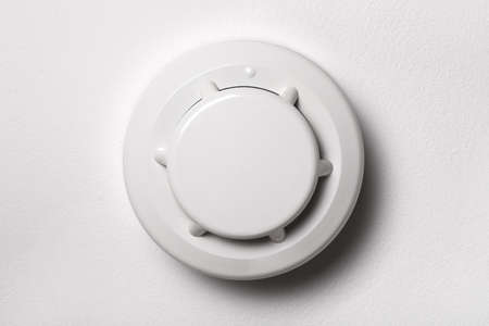 Smoke detector on the white ceiling. Stay home safe. Home control and security