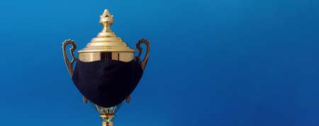 Winner gold cup in black protective mask, victory over coronavirus