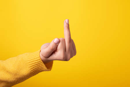 Hand sign showing middle finger in rude way meaning fuck off over yellow background