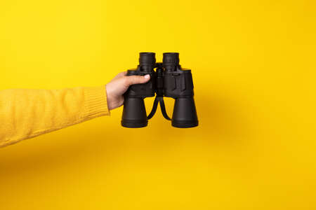 binoculars in hand over yellow background, search concept.