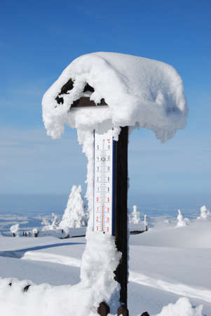 frozen snowy thermometer in winter mountains photo
