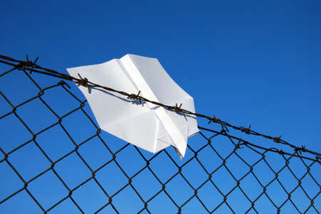 incarcerate: paper aeroplane cought in wire fence