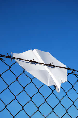 paper aeroplane cought in wire fence