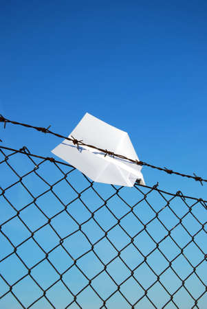 jailed: paper aeroplane cought in wire fence