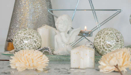 White ceramic angel with candles and holiday home decorations