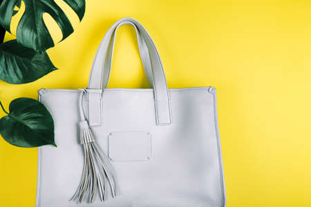 Grey colored stylish female hand bag with brush with monstera plant leaves composition on yellow background. Concep of accessories. Flat lay view.