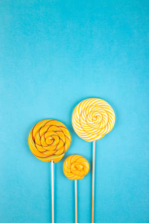 Three yellow  colorful lollipop candys arranged together on blue background. Flat lay concept.