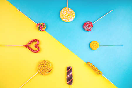 Many colorful lollipop candys arranged in circle form with empty space in the center on yellow and blue  background. Flat lay concept. background. Flat lay concept.
