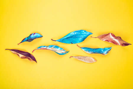 Vibrant vivid red, blue and yellow colored acrylic painted leaves on yelow background texture. Flat lay background.