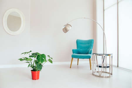 Conceptual light  interior of living room with blue armchair, metallic standing lamp,  glass round coffee table , oval mirror on white wall, monstera plant in red vase on the floor and large window. C 스톡 콘텐츠