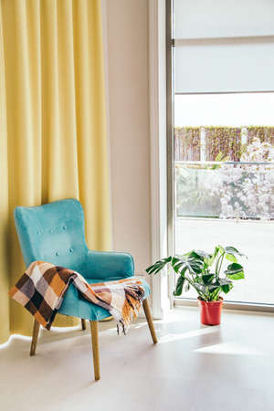 Conceptual light  interior of living room with blue armchair and brown blanket, monstera plant in red vase on white floor, large window and yellow curtain. Stockfoto