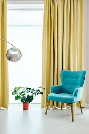 Conceptual light  interior of living room with blue armchair, metallic round shape standing lamp, monstera plant in red vase on the floor, large window and yellow curtain. 스톡 콘텐츠