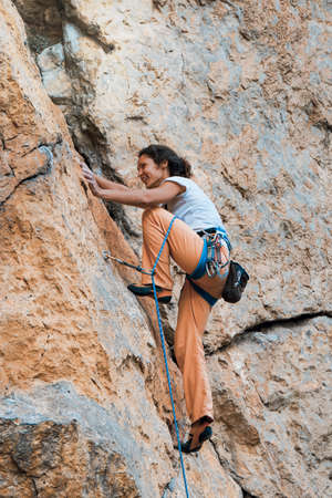Brunette hair woman climbs an overhanging yellow rock in Crimea peninsula, Red Stone rock. 免版税图像