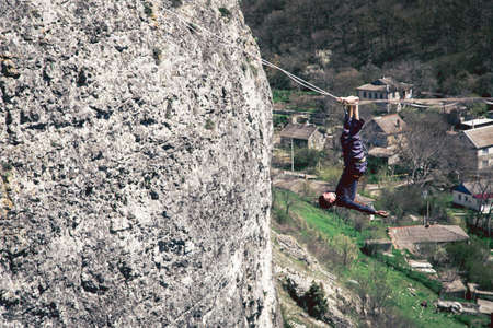 Man falling from high lina into the space in mountains. High line contest.
