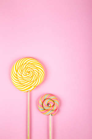 Two twisted round pink and green colorful lollipop candy placed on pink background. Flat lay concept.